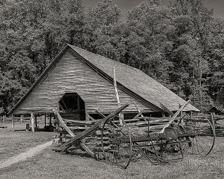 Black and White study of the barn and farm equipment at the Mountain Farm Museum, Oconaluftee Visitors Center, Great Smoky Mountains National Park. HDR image made from 3 separate exposures.