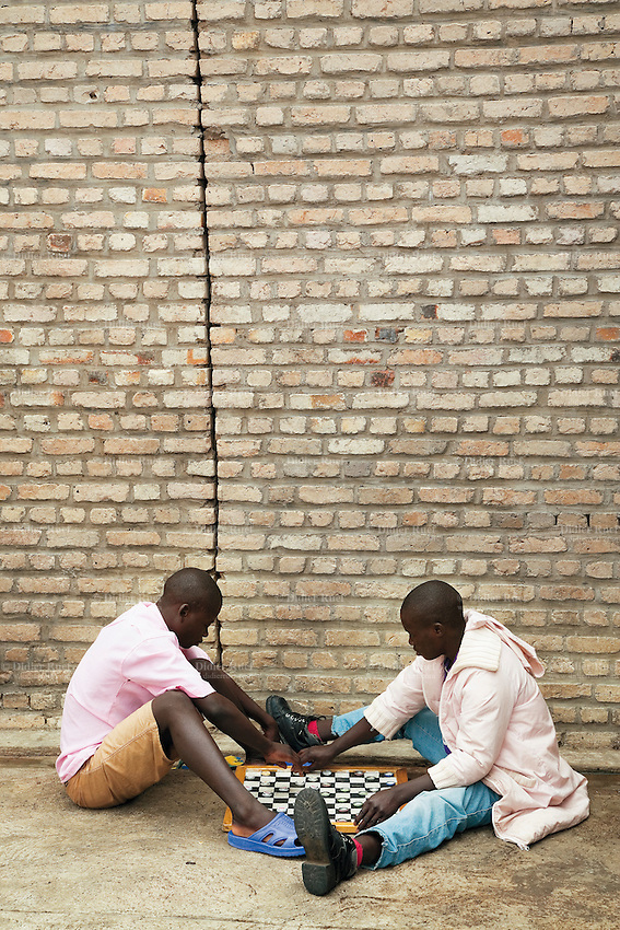 Rwanda. Southern province. District of Muhanga. Central jail of Gitarama. Two teenagers boys, wearing the pink prisoner's clothes, sit on the concrete ground and play the game of draughts. Bricks wall. Minors block. Minors in detention. Detention pending trial and after trial, when sentenced to prison. The non-governmental organization (NGO) Fondation DiDé - Dignité en détention runs the Encademi (Encadrement des mineurs) program. Prison centrale de Gitarama. Quartier des mineurs.  © 2007 Didier Ruef