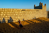 A child runs in the sand next to a wall in the Sahara Desert town of Boujbeja. /Felix Features