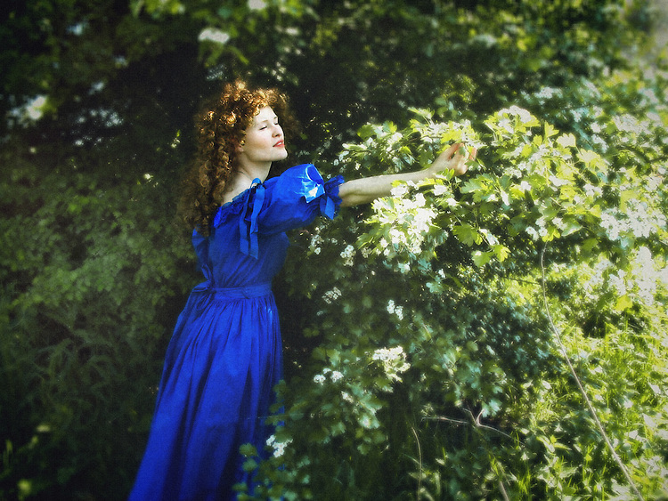A woman in a blue vintage gown and long red curly hair, standing in a garden and reaching one of the branches.