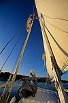 Egypt's Old Kingdom; Nile River scene; Aswan; Nubian sailor rests on foredeck of felucca; Egypt