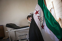 AMAS NAJIB plays with his son with a FSA flag at the clinic's office situated in a secret location at north of Syria.