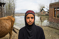 Apsa Darifa, 10, next to her house which was flooded in September in Purnishadashah village, Jammu and Kashmir, India, on 24th March 2015. Apsa had to flee her house in a boat when the floods came. She had no time to take any of her belongings. Save the Children supported her with an education kit to replace the school books she had lost. Photo by Suzanne Lee for Save the Children
