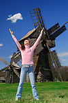 Young woman in the countryside with windmills in the background
