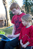 Kid Girl and Teenage Boy With Laptop Computer in Yard