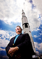 Photo by Gary Cosby Jr.  Jim Odom poses with the Saturn V rocket on display at the Space and Rocket Center.  Odom was the chief of engineering and tests of the Apollo second stage during his career.