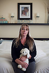 April Brune poses for a portrait while holding her son Ryan's stuffed dog on her bed in her Reno, Nevada home, February 3, 2014. Ryan Brune died from leukemia he was diagnosed with while they lived in Fallon, Nevada.