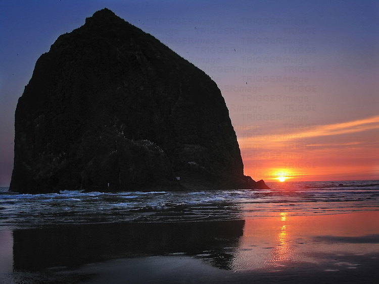A large rock on a beach and a sunset
