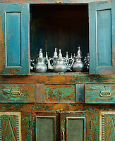 In the dining room a collection of silver teapots gleams against the emerald green doors of an antique hand-painted cupboard