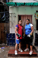 INDIA (West Bengal - Calcutta)July 2010,Shakila Babe(left) and Sanno Babe (right)  - standing in front of their house. Shakila and Shanno are twins from a poor muslim family of Iqbalpur, Kolkata. . Inspite of their late father's unwillingness to send his daughters to take up  boxing her mother Banno Begum inspired them to take up boxing at the age of 3. Their father was more concerned about the social stigma they have in their community regarding women coming into sports or doing anything which may show disrespect to the religious emotions of his community. Shakila now has been recognised as one of the best young woman boxers of the country after she won the  international championship at Turkey in the junior category. Shanno is also been called for the National camp this year. Presently Shakila and shanno has become the role model in the Iqbalpur area  and parents from muslim community of Iqbalpur have started showing interst in boxing. Iqbalpur is a poor muslim dominated area mostly covered with shanty town with all odds which comes along with poverty and lack of education. - Arindam Mukherjee