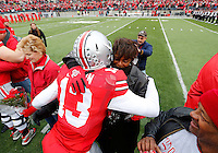 Ohio State Buckeyes quarterback Kenny Guiton (13) embraces a family member during Senior Day celebration before the college football game between the Ohio State Buckeyes and the Indiana Hoosiers at Ohio Stadium in Columbus, Saturday afternoon, November 23, 2013. The Ohio State Buckeyes defeated the Indiana Hoosiers 42 - 14. (The Columbus Dispatch / Eamon Queeney)