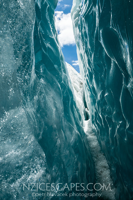 Walking through dark green, beautifully textured, glass like looking crevasse on Franz Josef Glacier, Westland Tai Poutini National Park, UNESCO World Heritage Area, West Coast, New Zealand, NZ