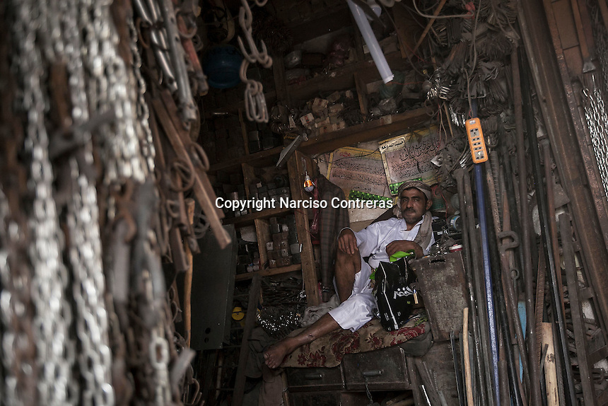 Monday 20 July, 2015: An iron seller is seen inside a shop in the iron-market place in the Old City of Sana'a, a 2,500-year-old cultural heritage site endangered after a fighter jet of the Saudi-led coalition bombed and destroyed a line of residential tower-houses killing 4 residents and reducing to rubble the historial site. The ongoing aerial campaign of bombardments by the Arab states and their western allies led by Saudi Arabia and the heavy fighting against the entrenchment of the Houthi insurgency along the Yemeni main cities from north to south has caused an international alert for the enlisted cultural heritage sites in Yemen, such as the historic town of Zabid, the Old City of Sana'a and the Old Walled City of Shibam. (Photo/Narciso Contreras)