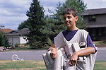 Young boy (9-10 yrs old) deliverying papers on his route, Bothell, Washington USA  MR