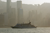 Cruise West ship &quot;Spirit of Oceanus&quot; sailing through Hong Kong's Victoria Harbour. The sun's rays can be seen cutting through the smog hanging over Central