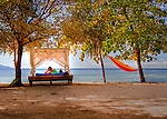 A guest lounges in a beach-side lounge cabana, enjoying the cool breeze and calm ocean view.  On the beach at the Siladen Resort and Spa, Siladen Island, Bunaken National Park, North Sulawesi, Indonesia.  (HDR image.)