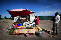 A woman sells fruit and vegetables from the back of her van on a roadside in Grozny.
