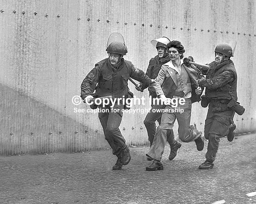 Snatch squad. On the 60th anniversary of the Easter Rising against British rule in Ireland, three British soldiers arrest a man outside Andersonstown Police Station, Belfast, N Ireland, Co Antrim. The man is believed to have been on his way to attend the annual republican Easter Commemeration ceremony in Milltown Cemetery located across the road from the police station. 197604005.<br />