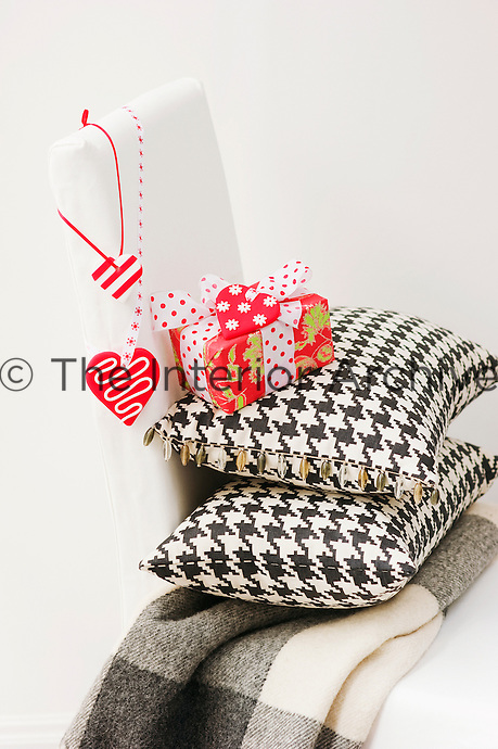 A beautifully wrapped Christmas present balances on a pair of cushions upholstered in Prince of Wales check