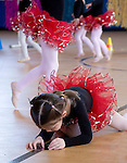 "Photo by Phil Grout..Budding ballerina, 4-year-old Sarah Rupprecht of Eldersburg,.pauses in the performance to explore her reflection in a shiny.electrical plate on the dance floor while the show goes on.featuring the ""Stepping Stars"" at the Freedom Fitness and Health.Expo."