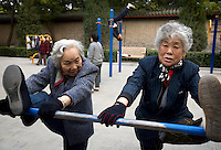 Elderly people perform morning exercise in a park..