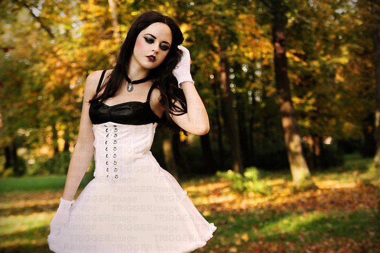 A girl with long black hair and pale skin dressed in a white dress and standing in an autumnal forest.