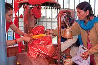 Kathmandu, Nepal.  Worshipers Tend to Hanuman Statue in a Neighborhood Temple.