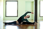 Real female dancer warming up in a beautiful exercise studio.