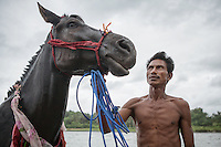 Johannes Ndara Kepala, a senior Pasola warrior, poses for photographs after he bathed his sandalwood horse at the nearby river of his village of Wainyapu.