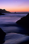 Cape Sebastian State Park Southern Oregon Coast along Highway 101 at sunset low tide with tidal pool reflecting setting moon and rock formations Oregon State USA..
