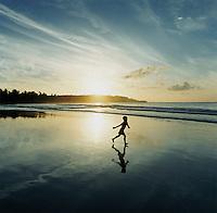 Boy Walking Next To His Reflection On A Beach Near Tangalle, Sri Lanka