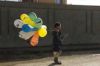 Boy selling balloons.