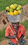 A woman carries mangoes in Mvula, Malawi...