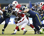 Seattle Seahawks defenders Red Bryant, left, and Alan Branch tackle Arizona Cardinals running back William Powell at CenturyLink Field in Seattle, Washington on  December 9, 2012.  The Seahawks beat the Cardinals 58-0.    ©2012. Jim Bryant Photo. All Rights Reserved.