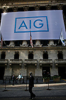 "People walk next to the entrance of New York Stock Exchange ""NYSE"" while  flag of American International Group is displayed on its building in New York. 15/10/2012. American International Group, Inc. (AIG) is a leading international insurance organization serving customers in more than 130 countries. Photo by Eduardo Munoz Alvarez / VIEWpress."