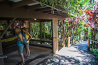 Two tourists read a sign and look at photos of the founders of the Hawai'i Tropical Botanical Garden in Onomea, Big Island of Hawaiʻi.