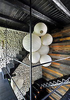 A contemporary staircase hallway with a dark wood beamed ceiling. Functional steps leading to the upper floor set against a wood clad and exposed stone wall. A group of paper globe lamp shades hang from the ceiling.