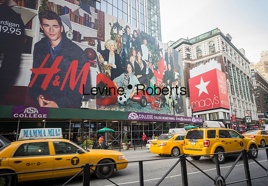 An enormous billboard announces the future arrival of an H&M department store at in Herald Square, across from Macy's, in New York, seen on Thursday, December 19, 2013. The 63,000 square foot store located in the Herald Center will be the department store's largest retail space and is in a vertical mall that originally was built for the now defunct E.J. Korvette discount department store chain which went out of business in 1980. (© Richard B. Levine)
