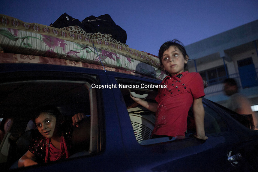 """August 26, 2014 - Gaza City, Gaza strip, Palestinian Territory: Displaced Palestinians pack their belongings to go back home after a new cease fire is announced between Hamas and Israel. The new cease fire marks the end of the """"Protective Edge"""" Israeli military operation in the Gaza strip. (Narciso Contreras/Polaris)"""