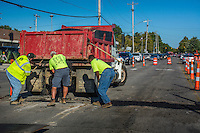 Construction workers pull asphalt from a truck to cover a small trench cut into the street during road construction.