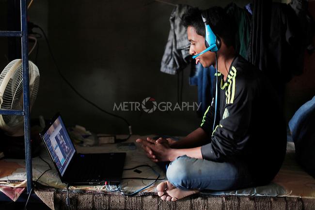 10/10/2014 -- Kirkuk, Iraq -- A Bangladeshi worker talks to his family via Skype in the garage in Kornish street.
