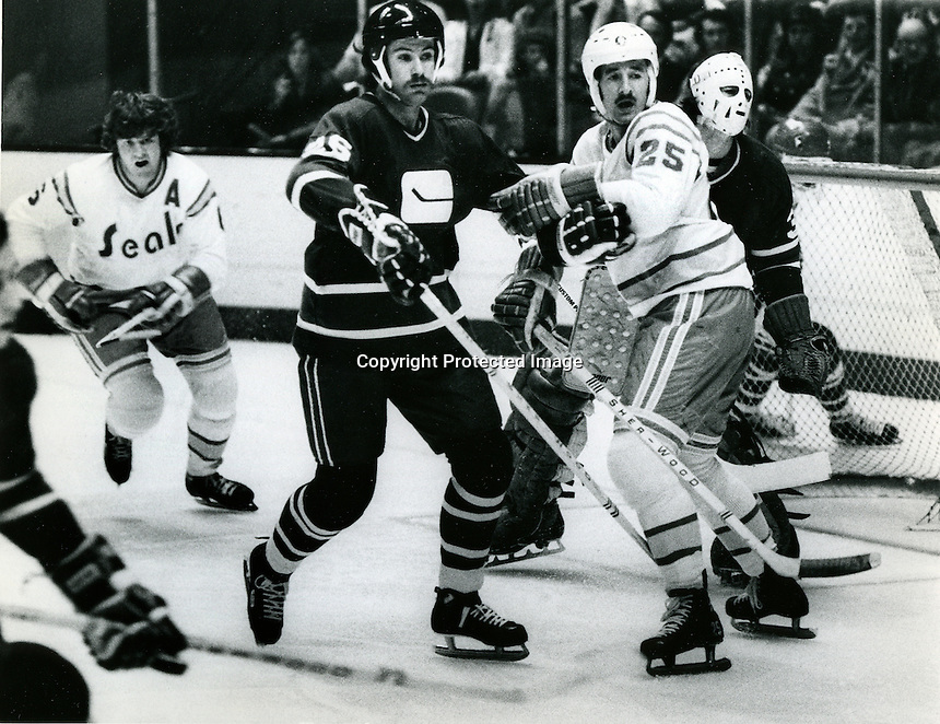 Seals action, Al MacAdam and Len Frig in the attack zone against Vancouver Canucks Bob Murray and goalie Ken Lockett.(photo by Ron Riesterer)