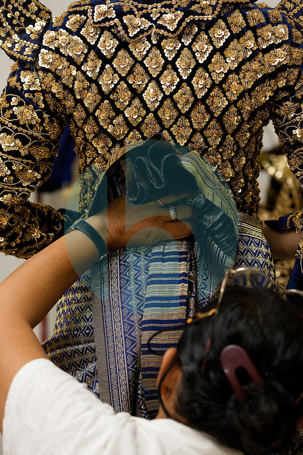 June 7th, 2008_Phnom Penh, Cambodia_ Dance troop members from the National School of Fine Arts, are literally sewn into their costumes, shortly before a performance of Anruch Preah Neang Ossa.  It has been some 50 years, since this classical Khmer dance piece was performed publicly and is being produced by the Amrita Performing Arts Association.   Photographer: Daniel J. Groshong/Tayo Photo Group
