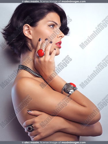 Beauty portrait of a young glamorous woman wearing jewellery with red stones