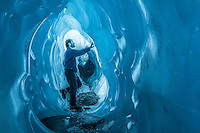 Man admires amazing textures and shapes of blue ice tunnel, cave on Franz Josef Glacier, Westland National Park, West Coast, World Heritage Area, South Westland, New Zealand