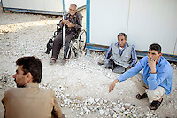 Khaled Jahmani sitting on the ground outside two shipping containers that have been made into a shelter for the elderly and disabled. Marwan Ghozlan, who helped organise the accomodation, squats down with them (blue shirt). Approximately two million people have fled the conflict in Syria. At least 130,000 of them live in Zaatari Refugee Camp, although it was designed to house 60,000, and a further 2,000 people arrive each day.