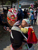 Hmong ethnic mother carrying baby on her back while using cellphone in Muong Hum market, Vietnam