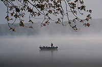 A fisherman steers his boat across fog shrouded Hoover Reservoir as the sun begins to rise on a Saturday morning.