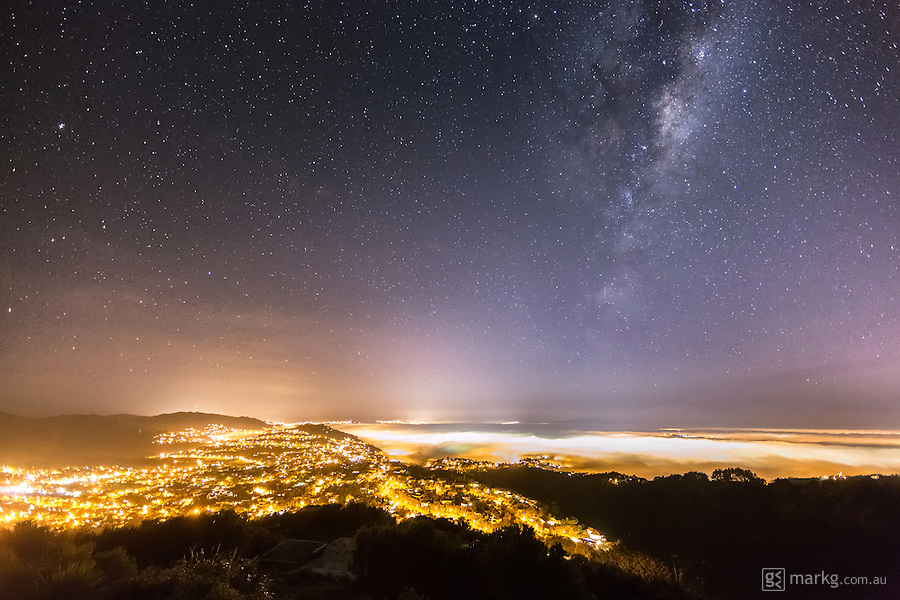 A heavy fog rolled into Wellington, New Zealand on the night of the 15th May 2013. This image was captured from Wrights Hill overlooking the city as The Milky Way rises high above in the night sky.