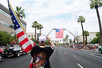 Phoenix, Arizona. July 7, 2013 - Nineteen hearses for each of the fallen members of the Granite Mountain Hotshots Arizona firefighting crew who died last week formed a procession to honor them in Phoenix as their bodies were taken back home to Prescott, about an 80-mile route. A lady carrying an American flag takes a photograph of the arc formed by two firetruck ladders and and large flag to honor the firefighters who died one week earlier on Sunday, June 30, as they were fighting a wildfire in Yarnell, Arizona. Photo by Eduardo Barraza © 2013
